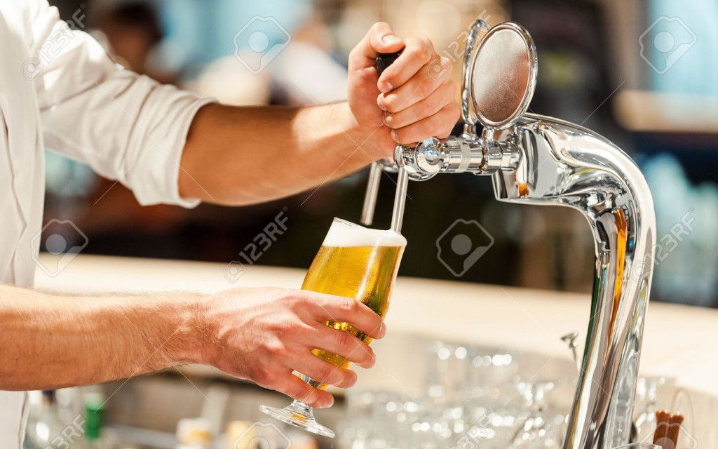 45811117-Pouring-fresh-beer-Close-up-of-young-bart